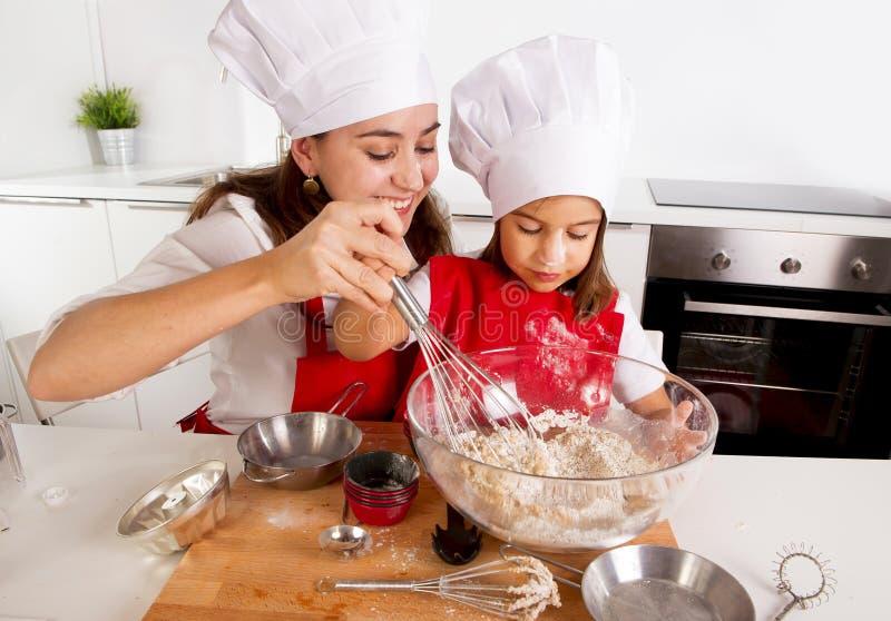 Gelukkig moederbaksel met weinig dochter in schort en kokhoed met bloemdeeg bij keuken stock afbeelding