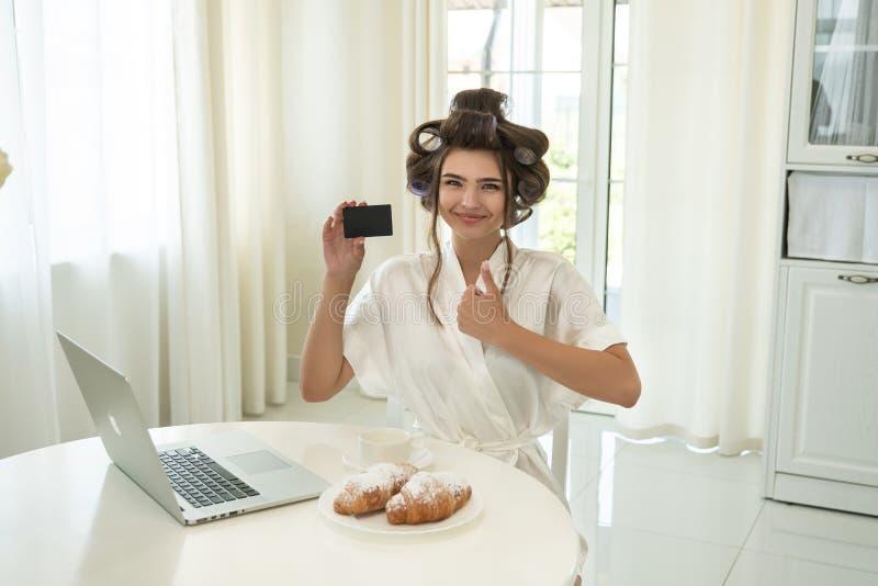 Gelukkig mooi jong brunette in haarkrulspelden die betaalpas houden die het succesvolle online winkelen op haar laptop hebben ter royalty-vrije stock fotografie