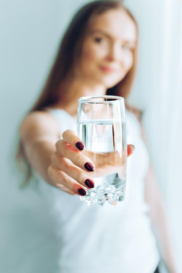 Gelukkig mooi jong vrouwen drinkwater Het glimlachen van Kaukasisch vrouwelijk modelholdings transparant glas in haar hand close- royalty-vrije stock afbeeldingen