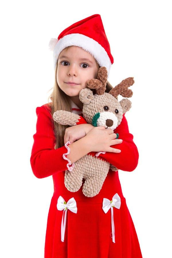 Gelukkig mooi Kerstmismeisje die het herten zachte stuk speelgoed koesteren, die een santahoed dragen over een witte achtergrond  stock foto