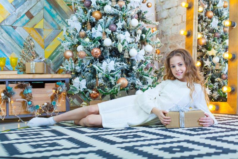 Gelukkig mooi kindmeisje met Kerstmisheden thuis op de vloer stock foto's