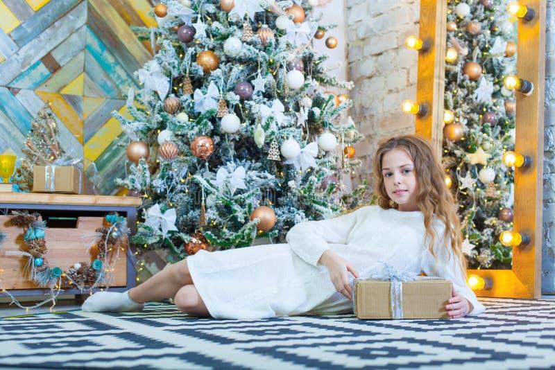 Gelukkig mooi kindmeisje met Kerstmisheden thuis op de vloer stock fotografie