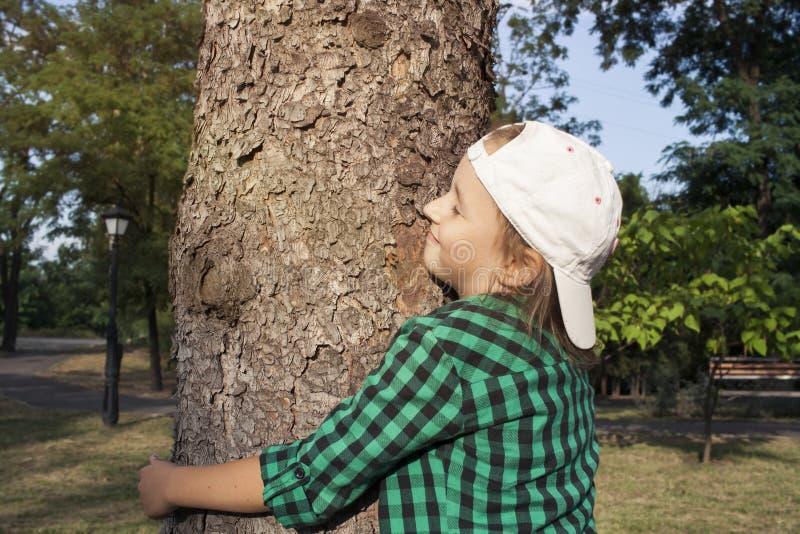 Gelukkig mooi meisje die grote boom in park koesteren Het houden van aard stock foto