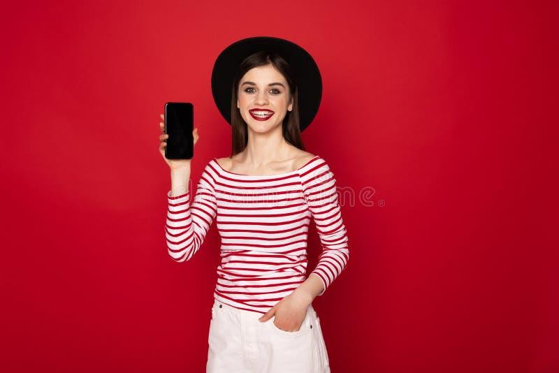 Gelukkig mooi meisje die het scherm van mobiele telefoon tonen stock afbeelding