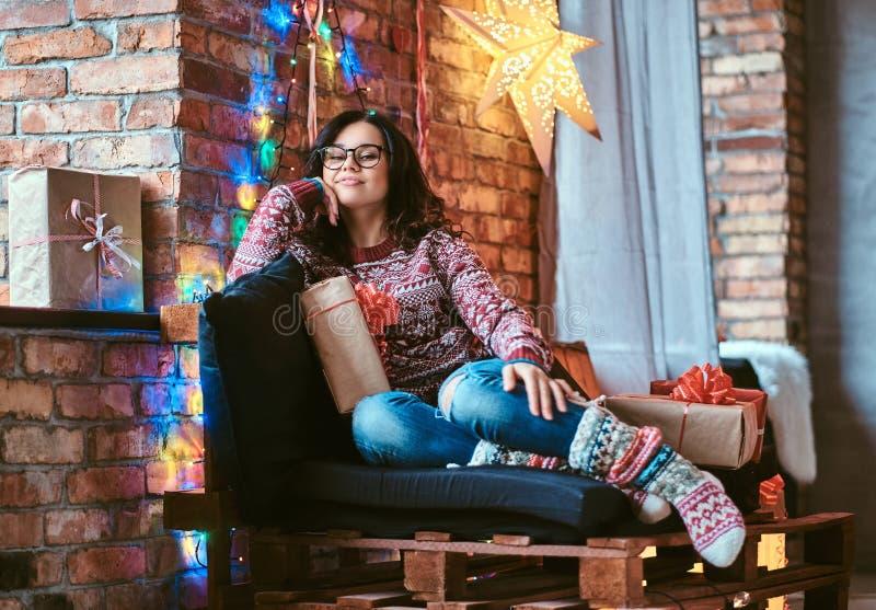 Gelukkig mooi meisje die Kerstmis van ochtend genieten terwijl het zitten op een laag met giftdozen in een verfraaide ruimte met  stock afbeeldingen