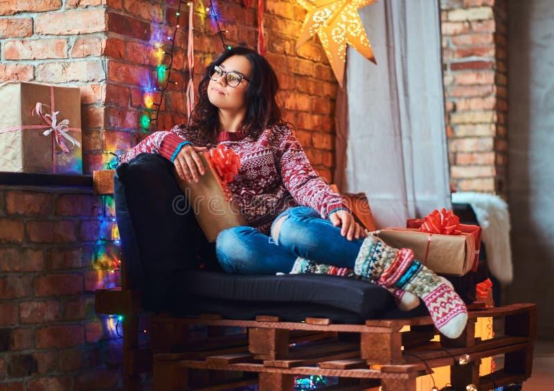 Gelukkig mooi meisje die Kerstmis van ochtend genieten terwijl het zitten op een laag met giftdozen in een verfraaide ruimte met  royalty-vrije stock afbeeldingen