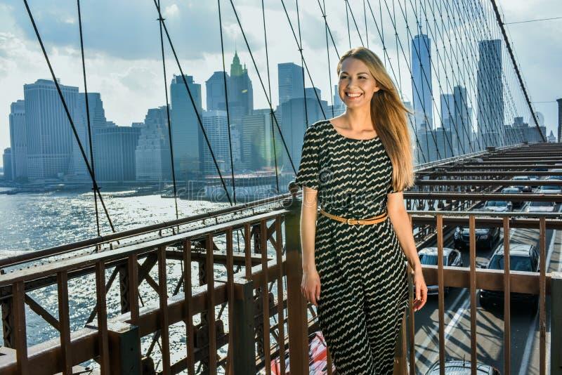 Gelukkig mooi meisje die terwijl status op een rivierbrug op een de zomer zonnige dag stellen royalty-vrije stock foto