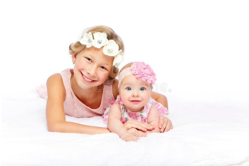Gelukkig mooi meisje met de zuster van de babybaby stock afbeelding