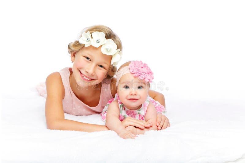 Gelukkig mooi meisje met de zuster van de babybaby stock afbeeldingen