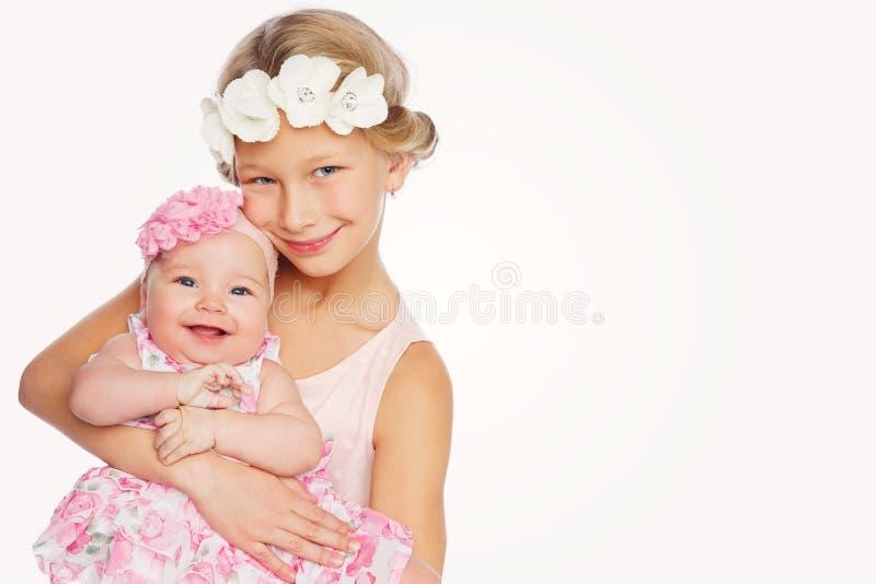 Gelukkig mooi meisje met de zuster van de babybaby stock fotografie