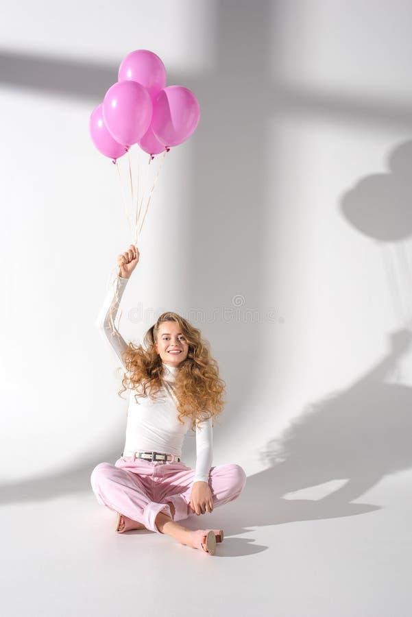 gelukkig mooi meisje met hand op zitting en holdingsbundel royalty-vrije stock afbeelding