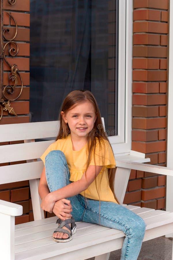 gelukkig mooi meisje met lang blondehaar die vrijetijdskleding dragen die op een bank zitten royalty-vrije stock foto