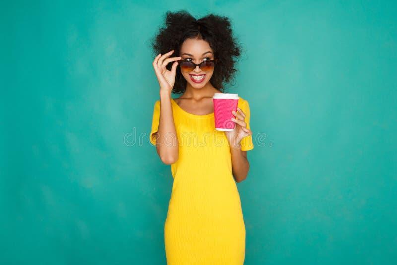 Gelukkig mulatmeisje die coffe bij studioachtergrond drinken royalty-vrije stock fotografie