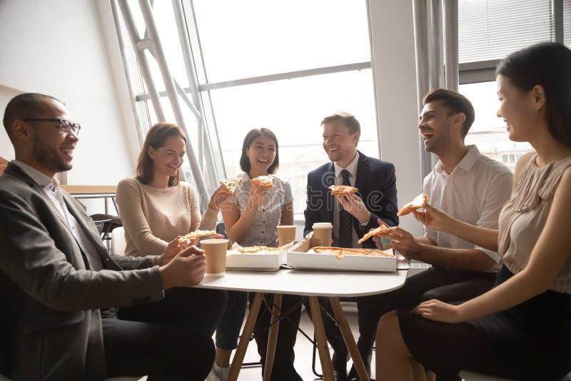Gelukkig multicultureel commercieel van personeelsarbeiders team die pret hebben die pizza eten stock foto
