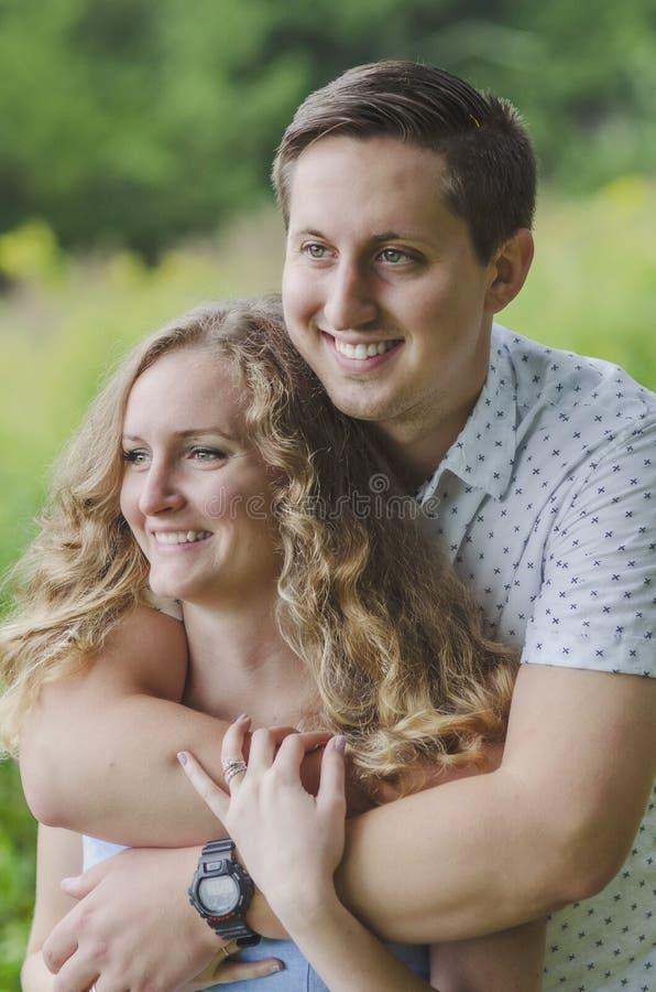 Gelukkig natuurlijk glimlachend jong paar die in openlucht koesteren stock afbeeldingen