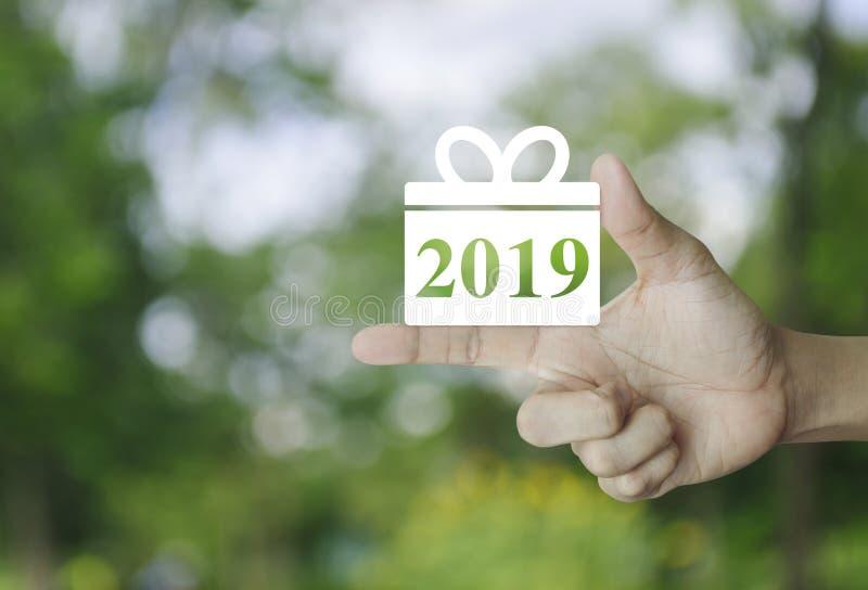 Gelukkig nieuw het jaar 2019 pictogram van de giftdoos op vinger over onduidelijk beeld groene boom in park, Bedrijfs het winkele stock afbeelding