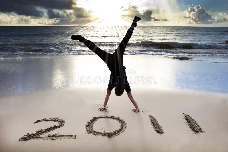 Gelukkig nieuw jaar 2011 op strand van zonsopgang stock foto's