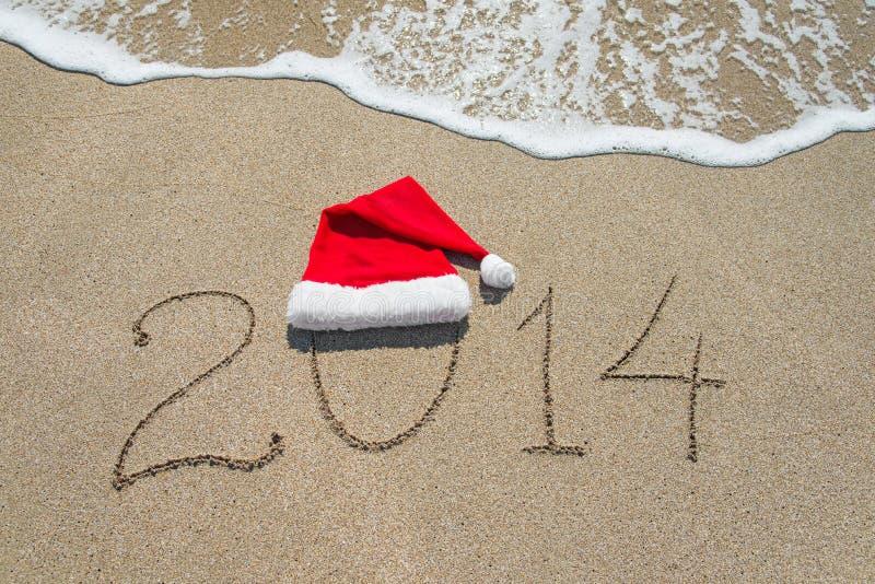Gelukkig nieuw jaar 2014 met Kerstmishoed op zandig strand - vakantie stock afbeelding