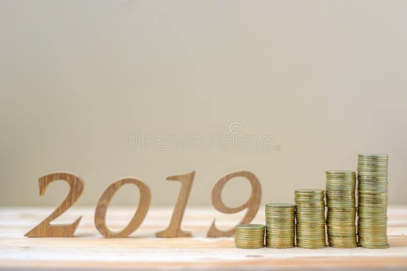 2019 Gelukkig Nieuwjaar met gouden muntstukkenstapel en houten aantal op lijst zaken, investering die, pensionering planning, fin royalty-vrije stock fotografie