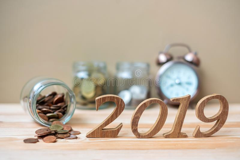 2019 Gelukkig Nieuwjaar met gouden muntstukkenstapel en houten aantal op lijst zaken, investering, pensionering planning stock foto
