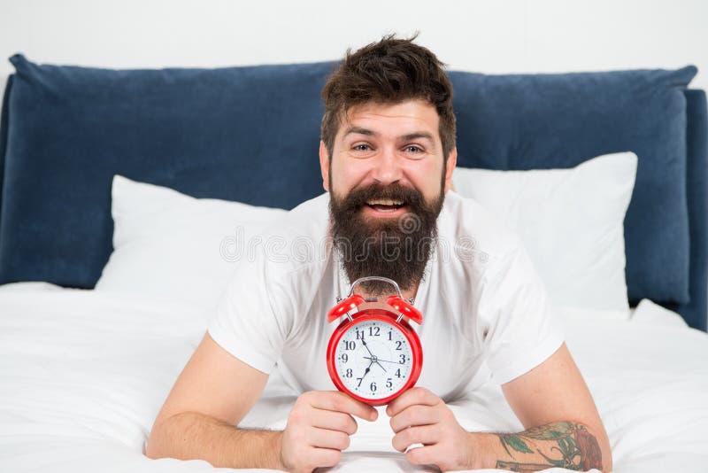 Gelukkig om de dag hier te beginnen brutale slaperige mens in slaapkamer rijp mannetje met baard in pyjama op bed in slaap en wak stock foto