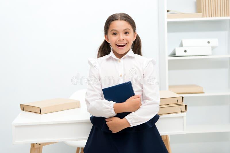 Gelukkig om in eerste vorm binnen te gaan Het meisjeskind houdt boektribune dichtbij lijst witte achtergrond Het schoolmeisje gen stock foto's