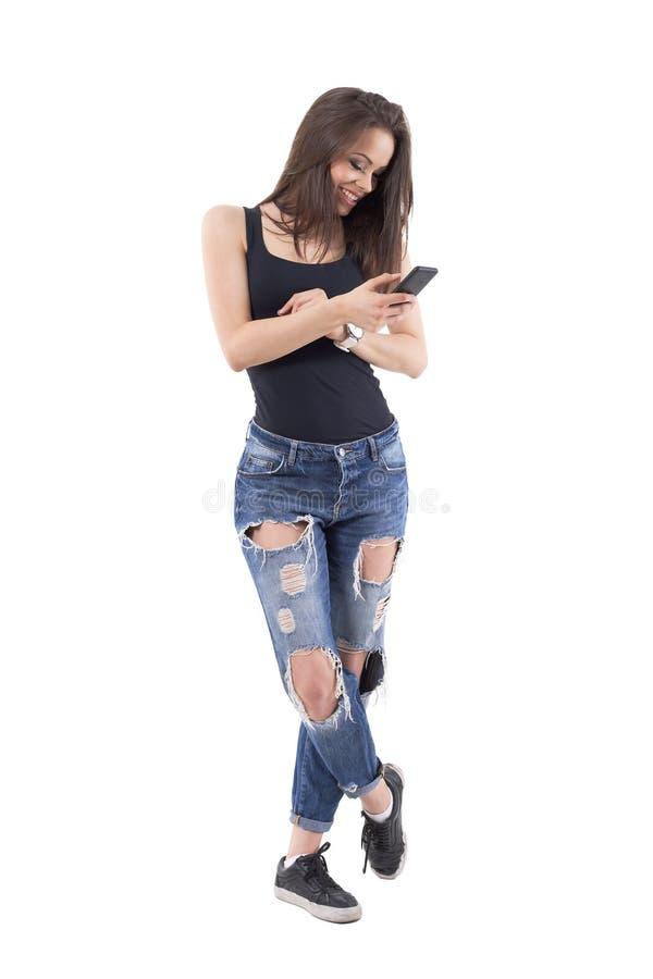 Gelukkig onbezorgd ontspannen jong wijfje die en berichten met mobiele telefoon verzenden lachen royalty-vrije stock afbeelding