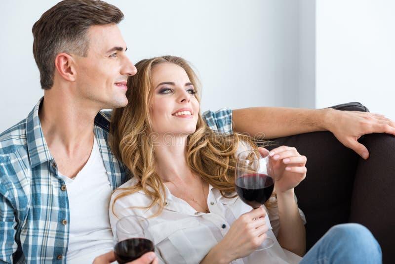 Gelukkig ontspannen paar die en rode wijn rusten drinken stock afbeeldingen