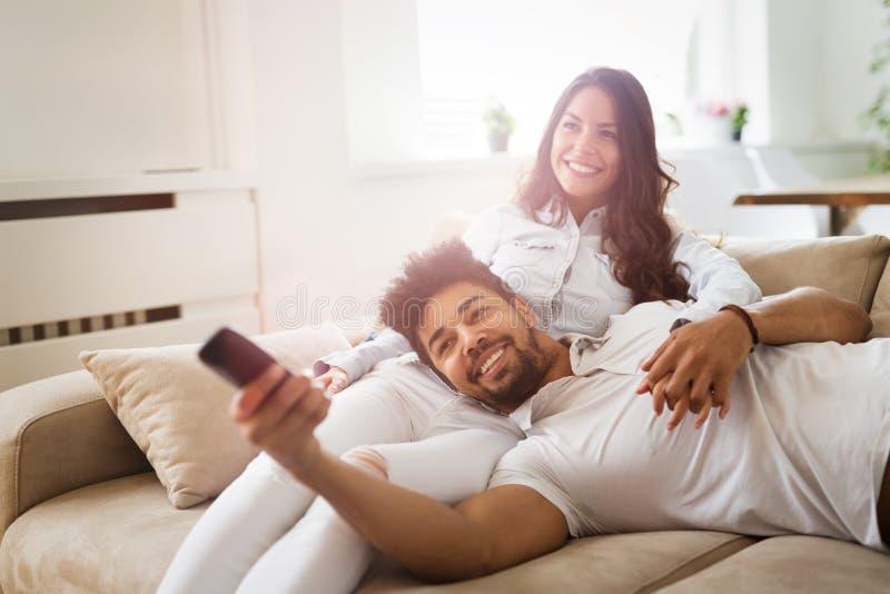 Gelukkig op bank liggen samen en paar die thuis ontspannen stock afbeelding