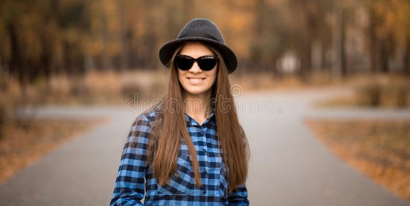 Gelukkig openluchtportret van jonge vrouw met hoed en zonnebril in daling, retro tonen van de stijlkleur royalty-vrije stock afbeelding