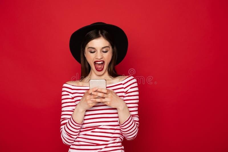 Gelukkig opgewekt meisjesoverseinen bij mobiele telefoon royalty-vrije stock fotografie