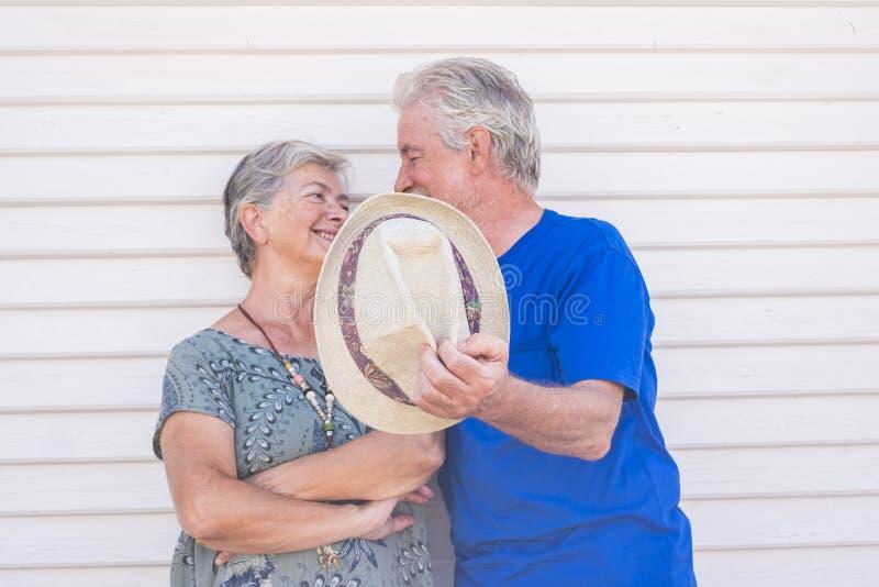 Gelukkig oud paar die met hoed in hand in een zonnige dag met witte houten achtergrond glimlachen - de vrolijke hogere mensen gen stock afbeelding