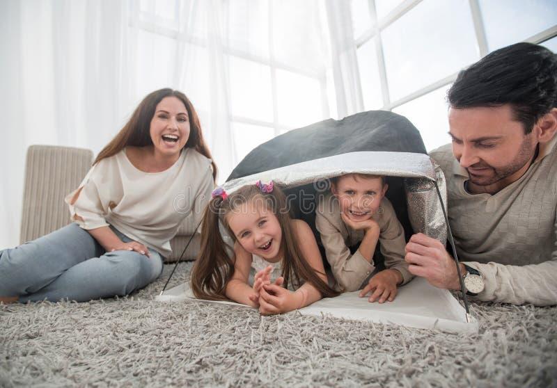 Gelukkig oudersspel met kinderen in een tent in de woonkamer stock foto's