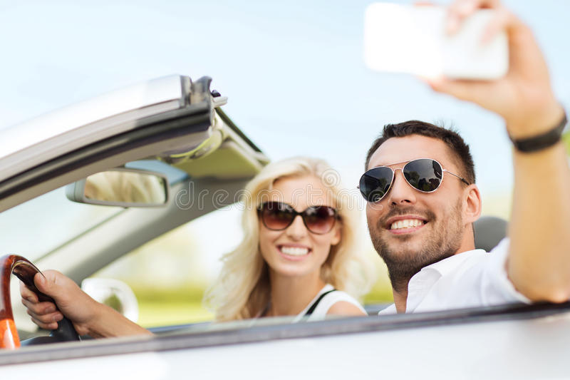 Gelukkig paar in auto die selfie met smartphone nemen royalty-vrije stock afbeelding