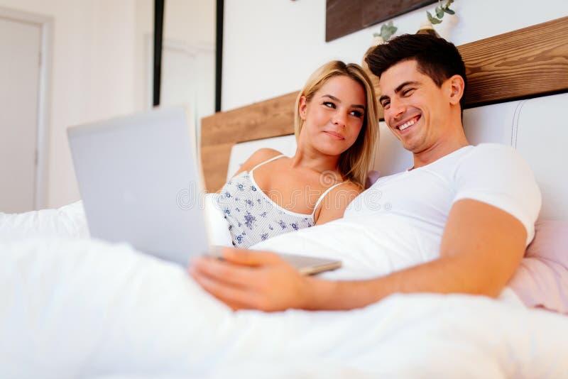 Gelukkig paar in bed die laptop met behulp van royalty-vrije stock fotografie
