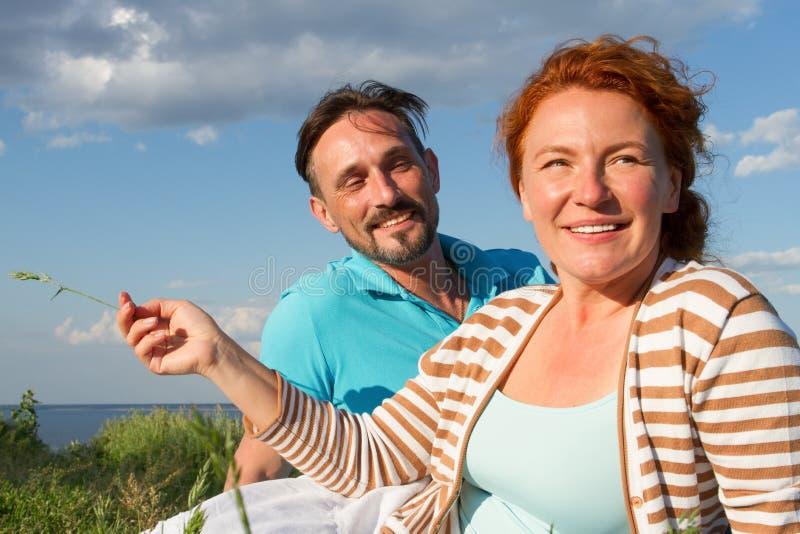 Gelukkig paar bij picknick Romantisch concept bij het strand Vrolijk paar die pret op de zomervakantie hebben stock afbeelding
