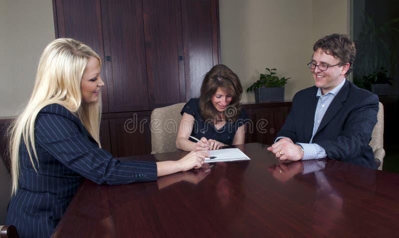 Gelukkig paar dat documenten met adviseur ondertekent royalty-vrije stock foto's