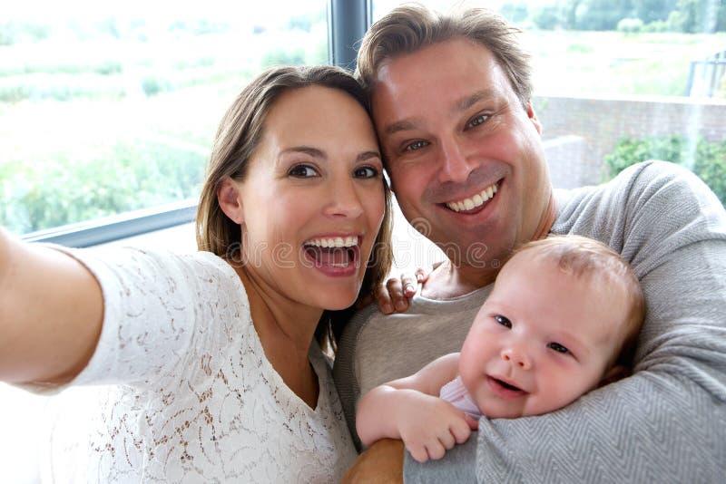 Gelukkig paar dat een selfie met baby neemt stock afbeeldingen