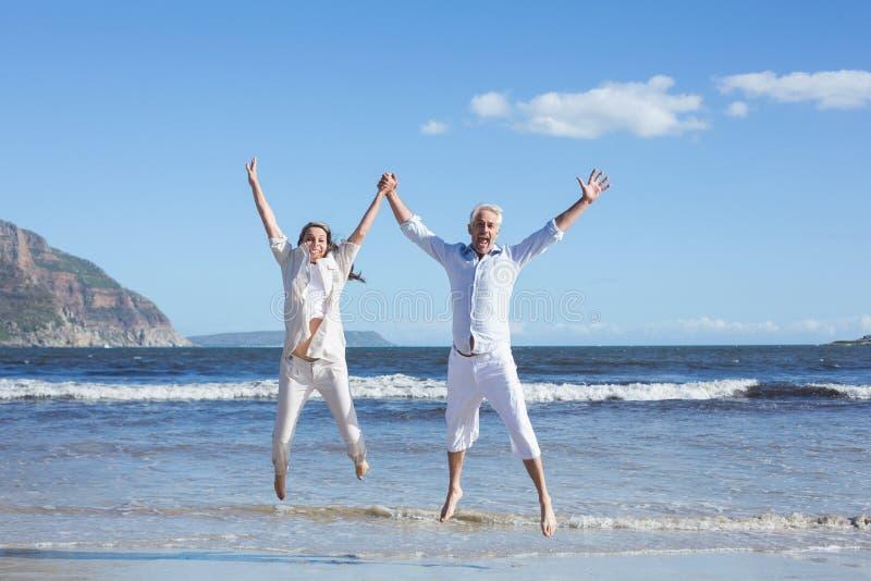Gelukkig paar dat omhoog blootvoets op het strand springt royalty-vrije stock afbeelding