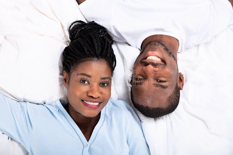 Gelukkig Paar dat op bed ligt stock afbeeldingen
