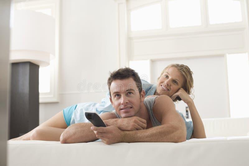 Gelukkig Paar dat op TV thuis let royalty-vrije stock foto