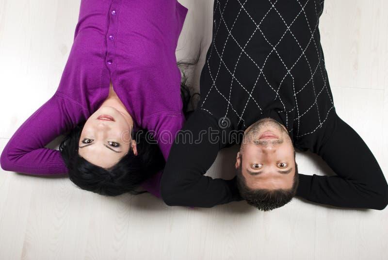 Gelukkig paar dat op vloer ligt stock fotografie