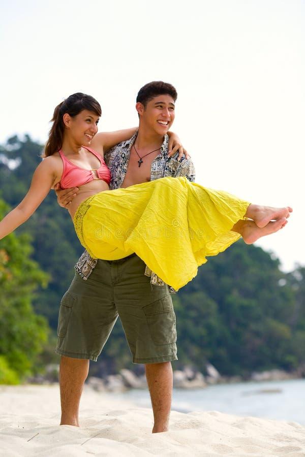 Gelukkig paar dat pret heeft bij het strand stock afbeelding