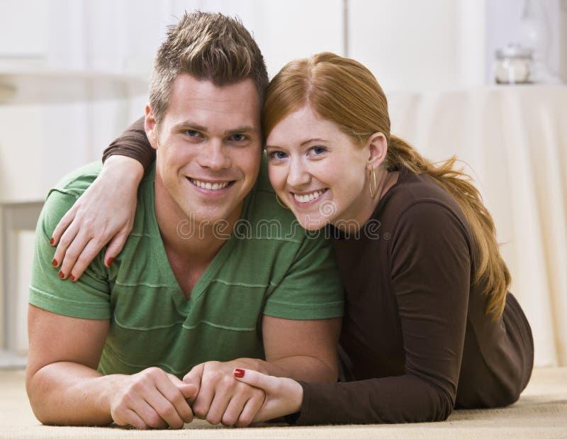 Gelukkig Paar dat samen op Hun Vloer ligt stock afbeeldingen