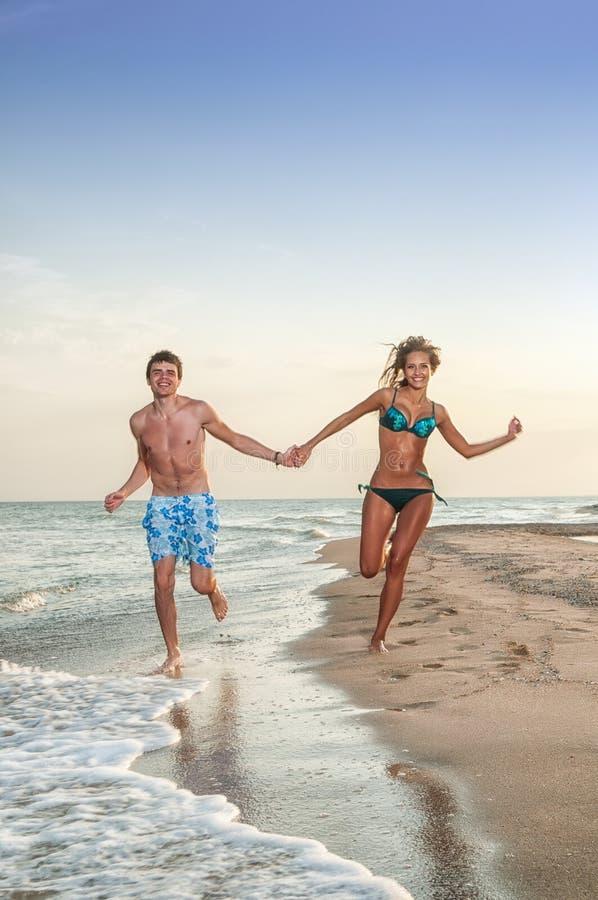 Gelukkig paar dat van vakanties op het strand geniet stock foto's