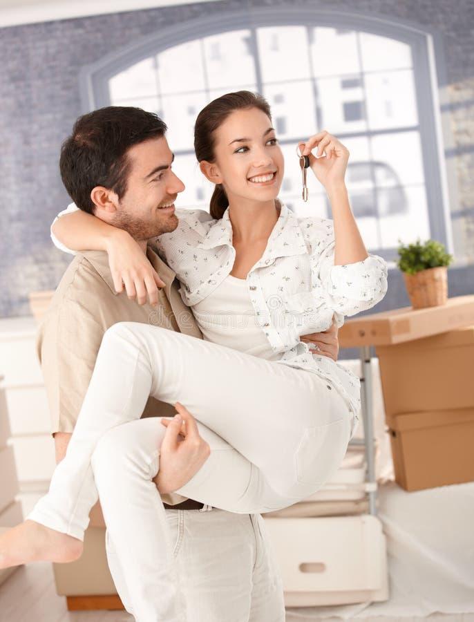 Gelukkig paar dat zich aan het nieuwe huis glimlachen beweegt