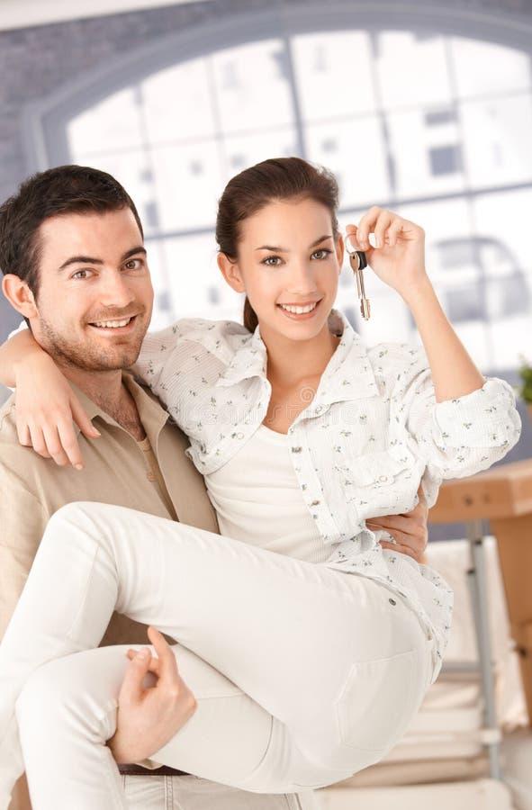 Gelukkig paar dat zich aan het nieuwe huis glimlachen beweegt royalty-vrije stock foto
