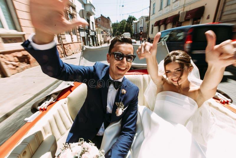 Gelukkig paar in de auto in de huwelijksdag stock fotografie