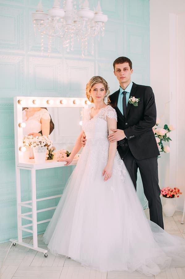 Gelukkig Paar De spruit van de huwelijksfoto in de witte studio met de kussen van het huwelijksdecor, omhelzingen royalty-vrije stock afbeelding