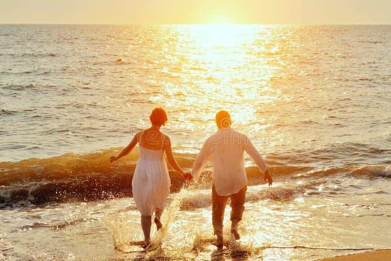 Gelukkig paar die aan overzees op het strand lopen stock foto